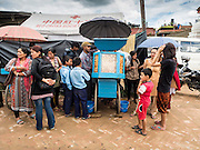 02 AUGUST 2015 - BHAKTAPUR, NEPAL:  People buy snacks from a street vendor in front of a small Internal Displaced Person (IDP) camp at Durbar Square in Bhaktapur for people left homeless by the Nepal earthquake. The Nepal Earthquake on April 25, 2015, (also known as the Gorkha earthquake) killed more than 9,000 people and injured more than 23,000. It had a magnitude of 7.8. The epicenter was east of the district of Lamjung, and its hypocenter was at a depth of approximately 15km (9.3mi). It was the worst natural disaster to strike Nepal since the 1934 Nepal–Bihar earthquake. The earthquake triggered an avalanche on Mount Everest, killing at least 19. The earthquake also set off an avalanche in the Langtang valley, where 250 people were reported missing. Hundreds of thousands of people were made homeless with entire villages flattened across many districts of the country. Centuries-old buildings were destroyed at UNESCO World Heritage sites in the Kathmandu Valley, including some at the Kathmandu Durbar Square, the Patan Durbar Squar, the Bhaktapur Durbar Square, the Changu Narayan Temple and the Swayambhunath Stupa. Geophysicists and other experts had warned for decades that Nepal was vulnerable to a deadly earthquake, particularly because of its geology, urbanization, and architecture.      PHOTO BY JACK KURTZ