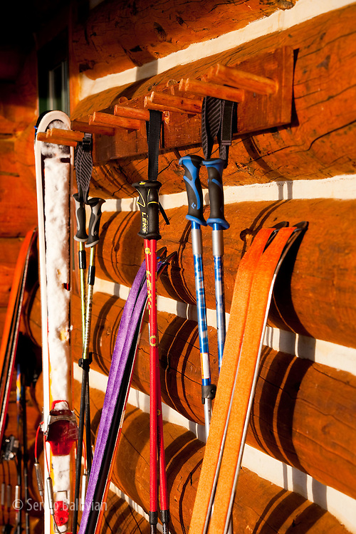 A graphic design is created by drying skis and climbing skins on the walls of Eiseman hut in Colorado.  Climbing skins adhere to the bottom of telemark and AT skis with glue in order to climb up hills while ski touring.