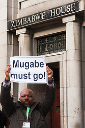 Lodon, February 21st 2015. Dozens of exiled Zimbabweans gather outside their embassy in London proclaiming Mugabe's last birthday in office. Singing and dancing as they have done every Saturday since 2002, the group spoke with passersby and added yet more names to their petition.