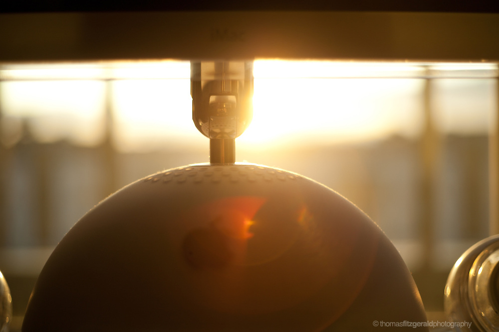"""A dramatic picture of the sunlight streaming through in the evening. The warm sun is illuminating an iconic """"lamp shade"""" Apple iMac"""