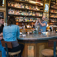 A waiter shakes a cocktail while customers enjoy their drinks at Sovereign Remedies, a bar and eatery located at 29 N Market Street in downtown Asheville, North Carolina.