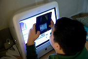 a boy playing a game on a handheld gaming device while sitting in front of a computer screen
