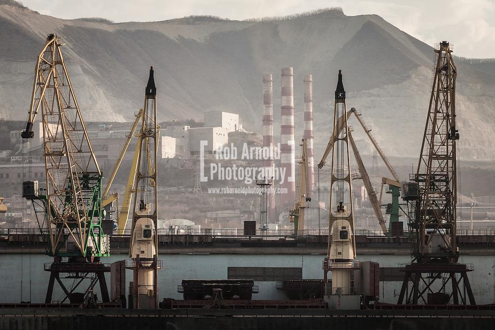 Industrial scene. Chimneys and cranes in the Russian Black Sea port of Novorossiysk