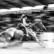 Dirt flies, as a cowgirl guides her horse around a barrel during the barrel racing competion.<br /> Augusta Rodeo 2011.