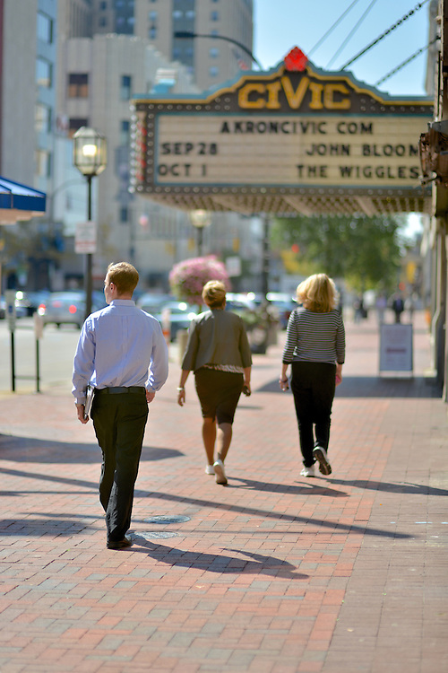 Pedestrians walking downtown outside of the Akron Civic Theatre.