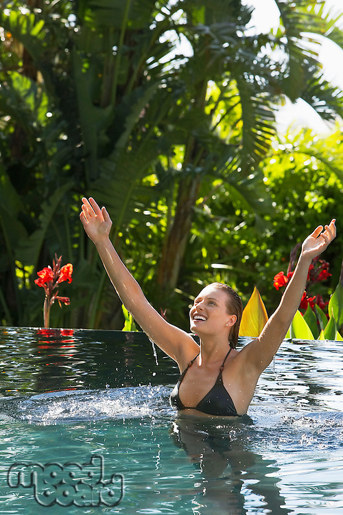 Young woman with raised arms in natural swimming pool portrait