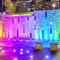 Charlotte Romare Bearden Park waterfall fountain wall with colorful lights at night. Panorama photo ratio is 1:3. Romare Bearden Park is a popular attraction in downtown Charlotte, North Carolina in the United States of America.