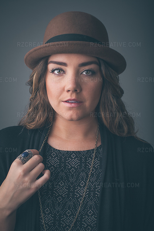Portrait of a beautiful woman wearing a black sweater and brown hat.