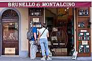 Couple shopping at Brunello Di Montalcino wine shop in ancient hill town of Montalcino in Val D'Orcia, Tuscany, Italy