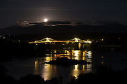 Once again I was lured by the evening light over the Menai Bridge. I never aim for those ever popular viewpoints but I drive past them almost daily so perhaps it's no surprise that ocassionally the view delivers something beyond the normal beauty it holds. <br /> <br /> The moon rose rapidly, shrinking in size by the minute as it did so. I only managed a few frames before the moon was obscured by cloud anyway, but I'm glad I stopped anyway to enjoy this very magical and serene moment.