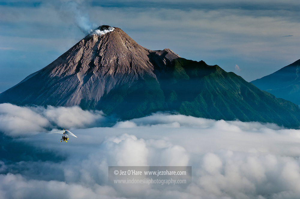 Trike microlight aircraft approaching Mount Merapi, Yogyakarta, Central Java, Indonesia