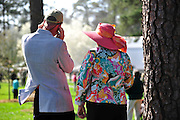 27 March 2010 : A man and woman, dressed in colorful spring attire stand in the paddock before the final race of the day.