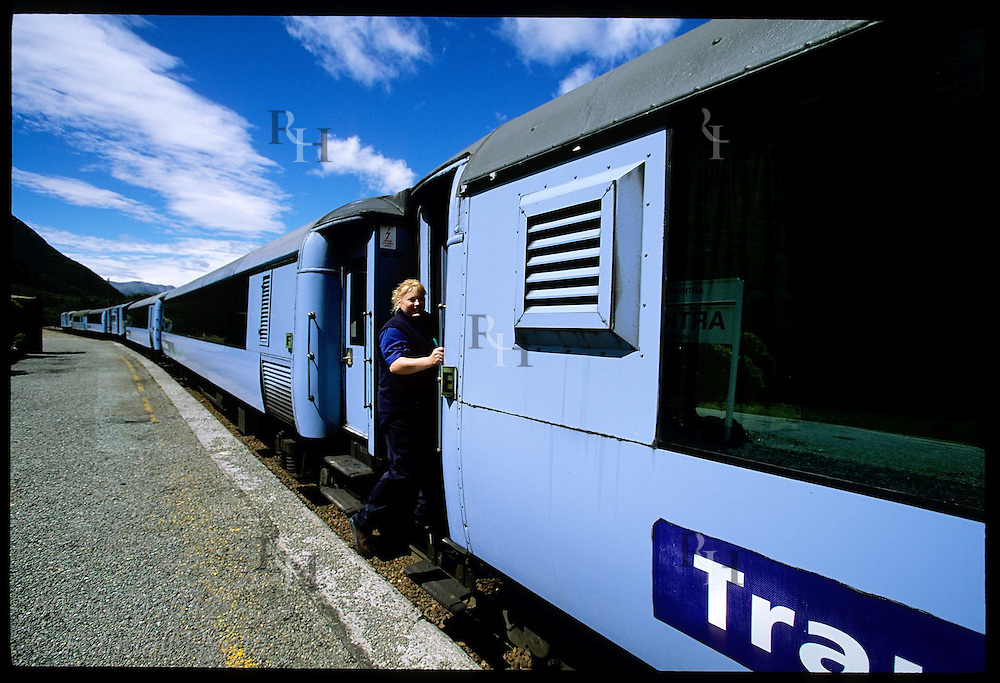 Female conductor jumps on TranzAlpine Express train as it departs Arthur's Pass village in the Southern Alps; New Zealand