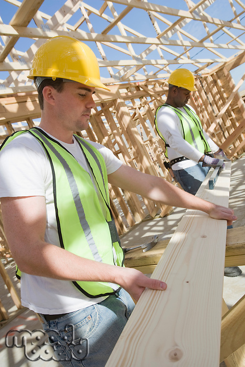 Two construction workers measuring wooden plank