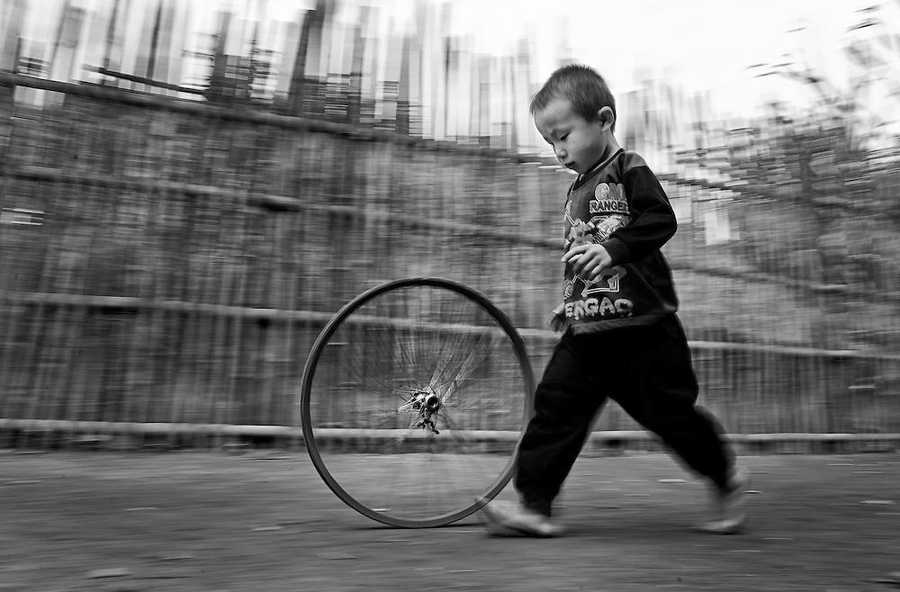 A Hmong boy plays with an old wheel near Luang Prabang, Laos.