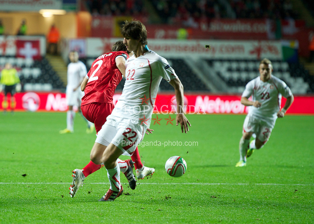 SWANSEA, WALES - Friday, October 7, 2011: Wales' Chris Gunter is fouled by Switzerland's Timm Klose resulting in a penalty kick during the UEFA Euro 2012 Qualifying Group G match at the Liberty Stadium. (Pic by Chris Brunskill/Propaganda)