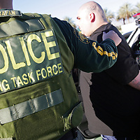 8:46 a.m. A man with a Penn West tattoo on the back of his head is in custody and taken out of a car after arriving at the Incident Command Post on Tuesday, December 7, 2010 during Operation Eastern Encore which is the largest gang sweep in Riverside County, Calif. history. Authorities say Penn West is an Indio, Calif.-based gang that was one of three targeted Tuesday. Crystal Chatham, The Desert Sun