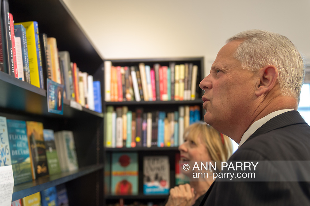 "Rockville Centre, New York, USA. April 201, 2018. Rep. STEVE ISRAEL browses through books before start of event for Nassau County debut of the former Congressman's (NY - Dem) newest novel ""Big Guns"" - a satire of the strong gun lobby, weak Congress, and small Long Island town. Store co-owner CAROL HOENIG is behind him. The talk and book signing was held at Turn of the Corkscrew Books & Wine store."