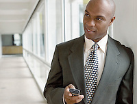 Businessman holding mobile phone in hallway