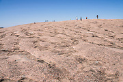 "Hikers explore atop a large pink granite dome at Enchanted Rock State Natural Area, between Fredericksburg and Llano, Texas, USA. Enchanted Rock is a fascinating exfoliation dome (with layers like an onion), rising 425 feet (130 m) above its surroundings to elevation of 1825 feet (556 m) above sea level, in the Llano Uplift. Geologically, the exposed rock (monadnock or inselberg, ""island mountain"") is part of a pluton (bubble of rock slowly crystallized from magma) within the billion-year-old igneous batholith, Town Mountain Granite (covering 62 square miles mostly underground), which intruded from a deep pool of hot magma 7 miles upwards into the older metamorphic Packsaddle Schist. The overlying sedimentary rock (Cretaceous Edwards limestone) eroded away to expose the prominent domes seen today: Enchanted Rock, Little Rock, Turkey Peak, Freshman Mountain, and Buzzard's Roost."