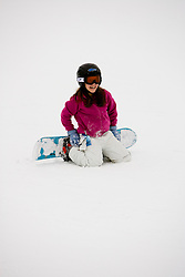 A girl (age 11) snowboarding at the Quechee Ski Hill in Quechee, Vermont. Model Release.