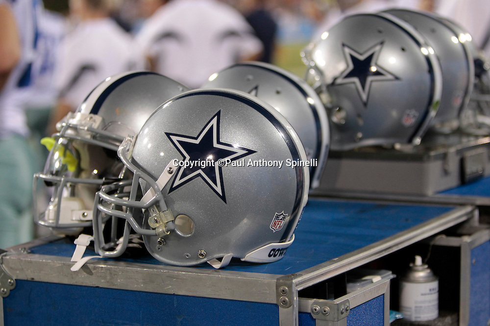 Dallas Cowboys helmets are lined up on the sidelines during the NFL Pro Football Hall of Fame preseason football game between the Dallas Cowboys and the Cincinnati Bengals on Sunday, August 8, 2010 in Canton, Ohio. The Cowboys won the game 16-7. (©Paul Anthony Spinelli)