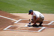 ANAHEIM, CA - JULY 10:  A groundskeeper works on home plate before the Los Angeles Angels of Anaheim game against the Seattle Mariners on July 10, 2011 at Angel Stadium in Anaheim, California. (Photo by Paul Spinelli/MLB Photos via Getty Images)
