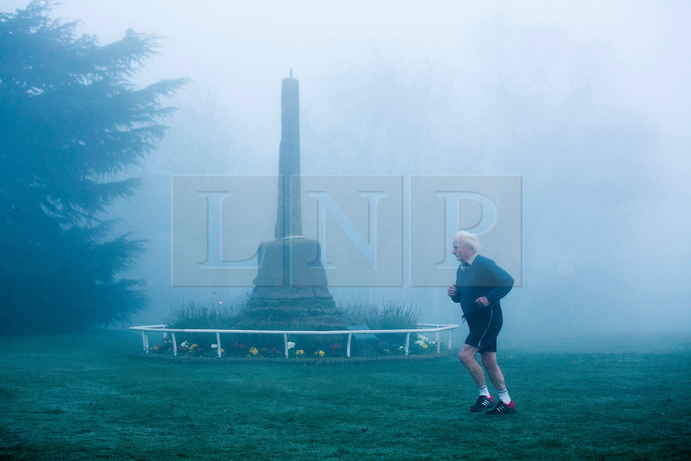 """© Licensed to London News Pictures. 14/03/2014. Meriden, Coventry, UK. Dense fog covered the Midlands earlier today. Pictured, a jogger makes his way past the """"Centre of England"""" monument in Meriden, near Coventry. Photo credit : Dave Warren/LNP"""