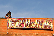 """20 AUGUST 2020 - DES MOINES, IOWA: A member of the Black Liberation Movement hangs a banner calling for justice for Black children during a vigil for missing Black children. About 150 people, members of and supporters of Des Moines Black Liberation Movement (which used to be known as Black Lives Matter) marched through a residential neighborhood of Des Moines Thursday night demanding justice for Black children. The march was called to show support for Breasia Terrell and  Abdullahi """"Abdi"""" Sharif, two Black children who went missing in Iowa this year. Terrell, a 10 year old girl,  went missing on July 10 and is still missing. Sharif, a teenager, disappeared from a Des Moines shopping mall in January, his body was found in May. Members of BLM said authorities have not adequately investigated the disappearances.     PHOTO BY JACK KURTZ"""