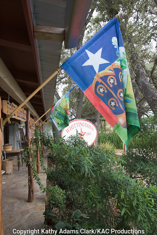 Yard flags with a Texas theme outside Whittington's Gift Shop in Johnson City, Texas.  boots, lone star.