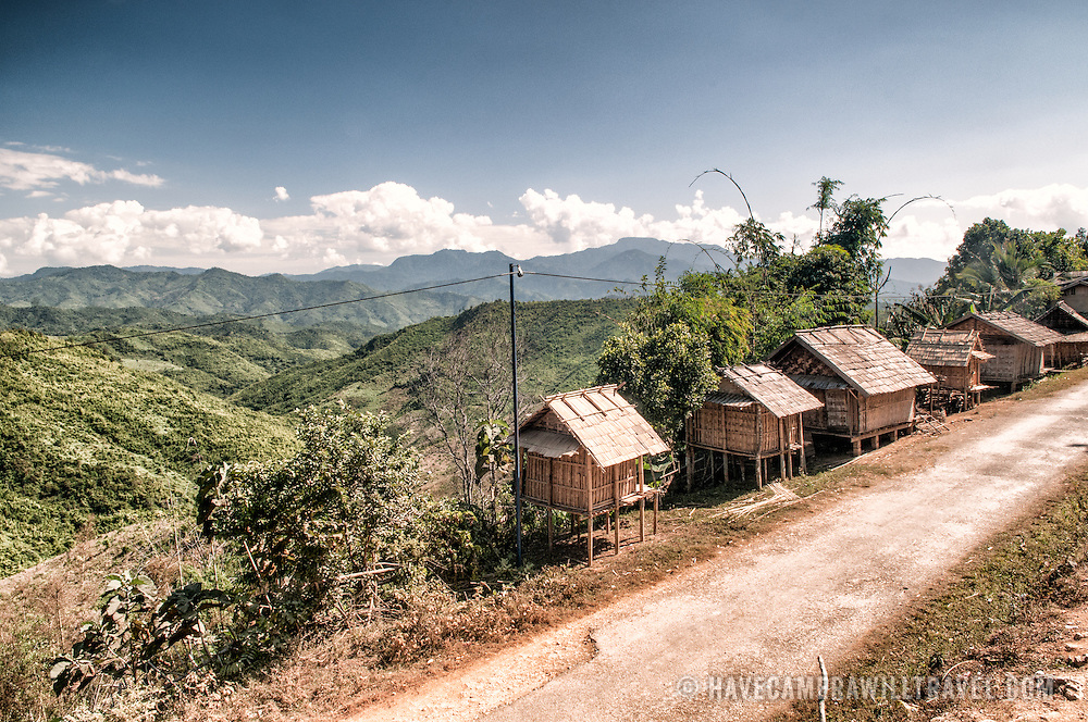 Rice storage huts on the side of the road in a remote village in the rugged terrain of northern Laos.