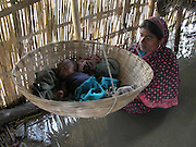 zahura biwi of paban mondal's village is seeing her just new  born baby because  floodwaters inundate her house at fekamari village, about 330 kilometers (206 miles) southwest of Gauhati, capital of northeastern Indian state of Assam, thurshday, July 10, 2003. Floods and mudslides in the northeastern states of Assam and Tripura have killed at least six people over the past week and uprooted more than 500,000 from their homes. (AP Photo/Shib Shankar Chatterjee)