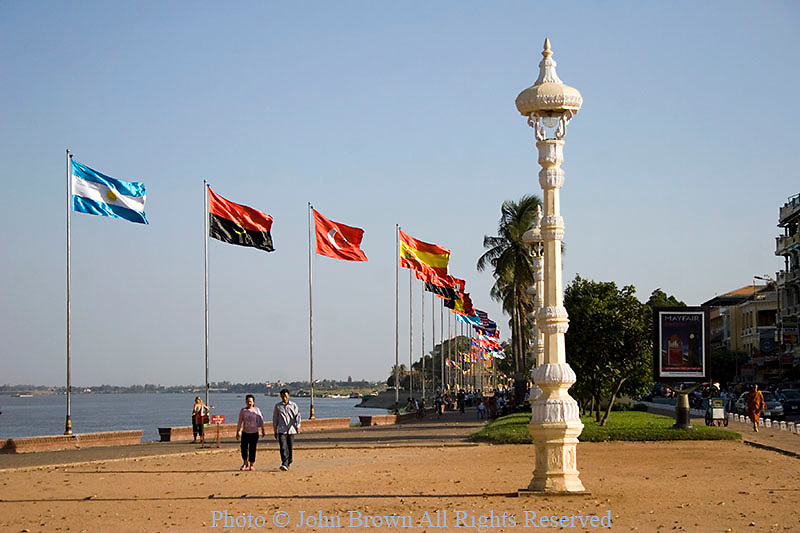 A group of flags are flying on the riverside promenade near the Mekong River in Phnom Penh, Cambodia.