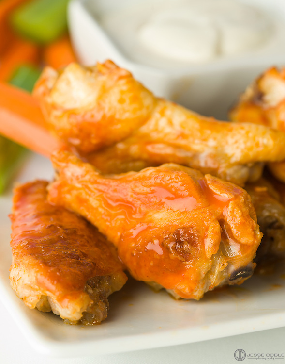 Hot wings on a plate with carrots and celery.