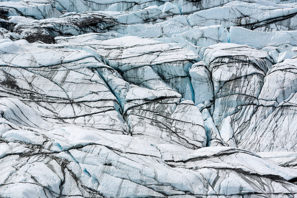 Rock debris, crevasses and seracs create abstract patterns in the terminus of Matanuska Glacier in Southcentral Alaska. Spring. Afternoon.