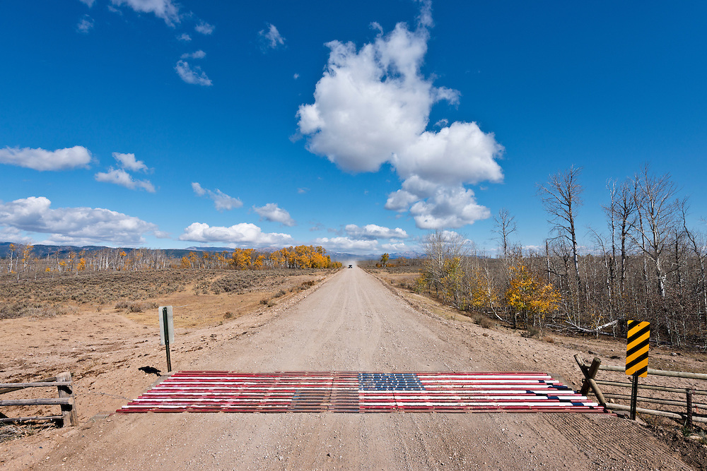 Patriotic American Flag cattle guard on country road in Eastern Idaho with a few autumn colors still hanging on and a pick-up truck in the distance travel toward cattle guard