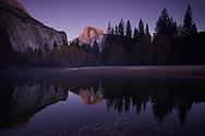 The granite wall of Half Dome reflects the evening twilight in Yosemite National Park, California.