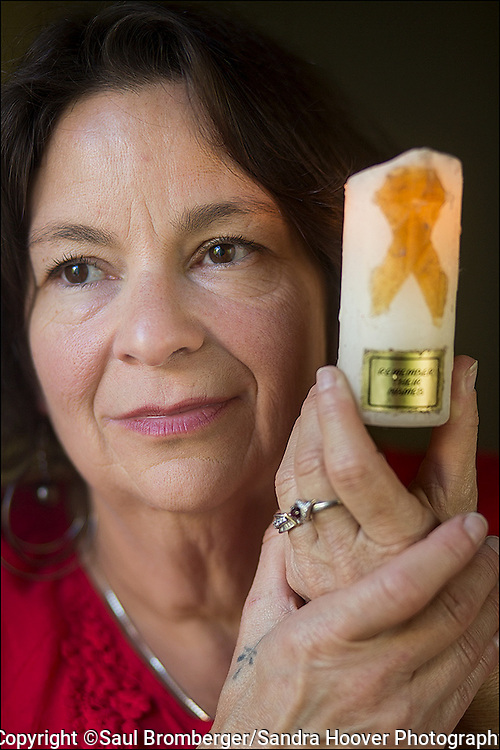 Portrait of the AIDS Generation --<br /> Betsy Ponce, a Long Term HIV Survivor, holding a candle she held at an AIDS Memorial march in the early 1990's, at her home in San Francisco, CA.