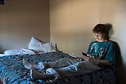 Christian Akridge checks his social media at his home in Wichita Falls, Texas on November 18, 2015.  (Cooper Neill for Rolling Stone)