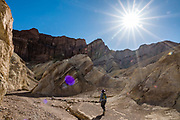 Sunburst over Red Cathedral. Hike scenic Golden Canyon Trail to Red Cathedral then loop back via Gower Gulch (6 miles with 800 ft gain), in Death Valley National Park, California, USA.