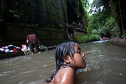 A girl swims in a small stream running through Ubud Bali,Indonesia.