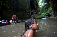 A girl swims in a small stream running through Ubud Bali,Indonesia.