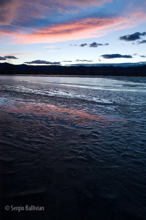 A winter sunset over a frozen lake in the Rocky Mountains near Boulder, Colorado