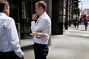 A businessman holds a wrapped up takeaway baguette while talking to a colleague in the City of London, the capital's financial district, on 17th June 2019, in London, England.