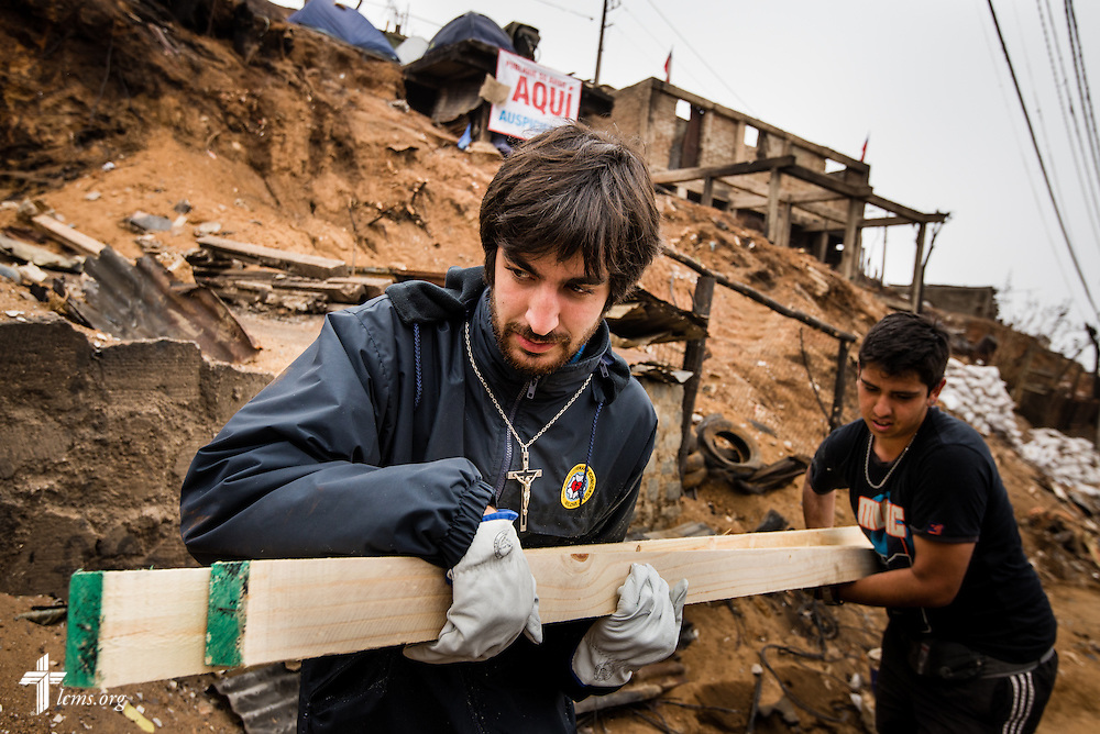 The Rev. Juan Pablo Lanterna of the Confessional Lutheran Church of Chile carries building supplies up a hillside scarred by fire on Tuesday, April 22, 2014, in Valparaíso, Chile. A catastrophic fire in the hillsides killed 15 people, destroyed about 3000 homes, and left approximately 15,000 people homeless.  LCMS Communications/Erik M. Lunsford