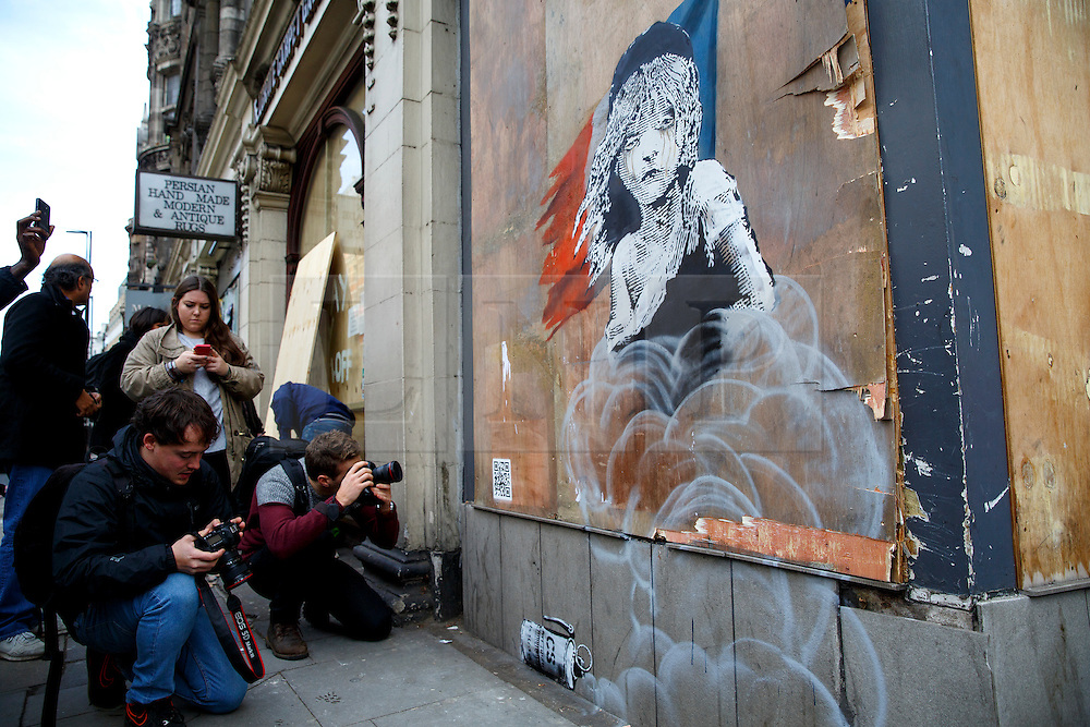 © Licensed to London News Pictures. 25/01/2016. London, UK. Members of media photographing a new Banksy mural criticising the use of teargas on refugees in Calais has appeared on a building opposite the French Embassy in London on Monday, 25 January 2016. Photo credit: Tolga Akmen/LNP