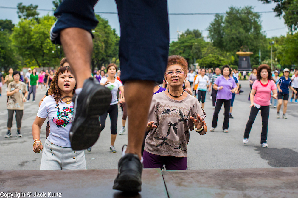06 OCTOBER 2012 - BANGKOK, THAILAND: Class participants follow their instructor during a public exercise class in Lumphini Park in Bangkok. The Thai government promotes exercise classes as a way staying healthy. Lumphini Park is 142 acre (57.6-hectare) park in Bangkok, Thailand. This park offers rare open public space, trees and playgrounds in the congested Thai capital. It contains an artificial lake where visitors can rent boats. Exercise classes and exercise clubs meet in the park for early morning workouts and paths around the park totalling approximately 1.55 miles (2.5km) in length are a popular area for joggers. Cycling is only permitted during the day between the times of 5am to 3pm. Smoking is banned throughout the park. The park was created in the 1920's and named after Lumbini, the birthplace of the Buddha in Nepal.   PHOTO BY JACK KURTZ