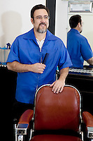 Happy mature man with comb in barbershop