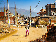 02 MARCH 2017 - SANKHU, NEPAL: A woman walks through the still devastated center of Sankhu. The town was badly damaged in the 2015 earthquake. Although there is more construction and rebuilding going on in Sankhu, west of central Kathmandu, than in many other parts of the Kathmandu Valley, many neighborhoods are still empty.  In some villages in the Kathmandu valley workers are working by hand to remove ruble and dig out destroyed buildings. About 9,000 people were killed and another 22,000 injured by the earthquake. The epicenter of the earthquake was east of the Gorka district.   PHOTO BY JACK KURTZ