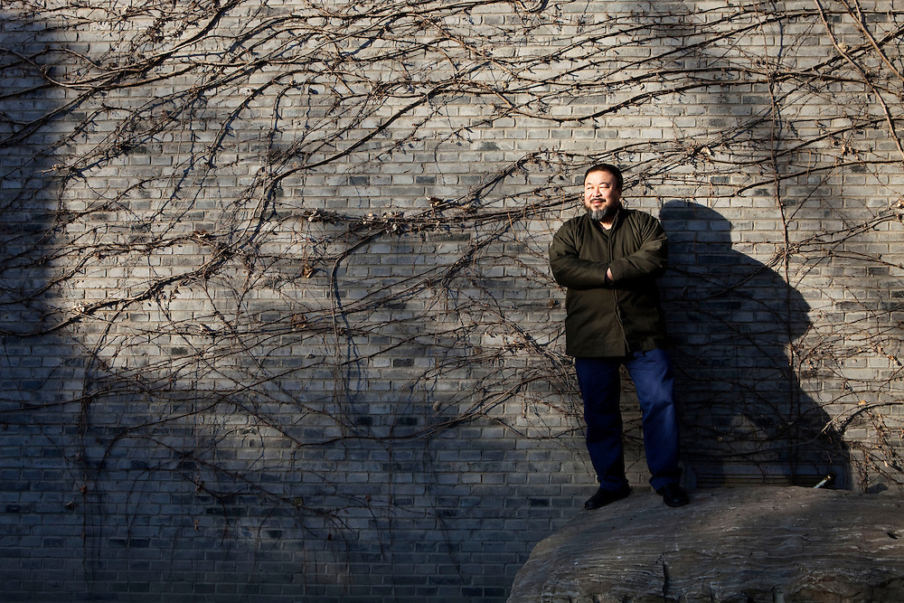 """Ai Weiwei, (born 1957, Beijing) in his courtyard at his studio. He is a leading Chinese artist, curator, architectural designer, cultural and social commentator and activist. Ai is known for the design of the Beijing National Stadium, more commonly known as the """"Bird's Nest"""", the main stadium of the 2008 Olympic Games in Beijing. Beginning with the 2008 Sichuan earthquake, Ai has emerged as one of China's most influential bloggers and social activists; he is known for his tongue-in-cheek and sometimes vulgar social commentary, and has had frequent run-ins with Chinese authorities. He was particularly focused at exposing an alleged corruption scandal in the construction of Sichuan schools that collapsed during the earthquake.Born in Beijing, his father was Chinese poet Ai Qing, who was denounced during the Cultural Revolution and sent off to a labor camp in Xinjiang with his wife, Gao Ying. Ai Weiwei also spent five years there. Ai Weiwei is married to artist Lu Qing. Ai Weiwei is represented by Galerie Urs Meile Beijing-Lucerne. Beijing, China. 2010"""